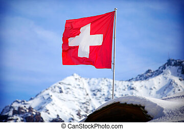 Switzerland flag Over Swiss Mountains in a Winter Day