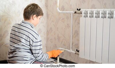 Boy paints a heating radiator in  apartment