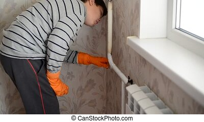 Boy paints a heating radiator in apartment - Boy paints a...