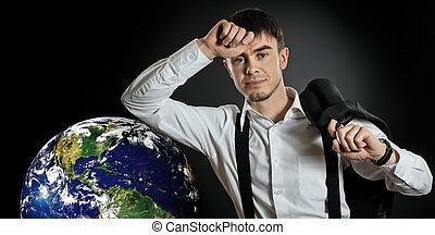 businessman hold in hand terrestrial globe, on dark blue...
