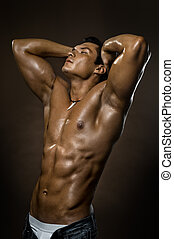 bodybuilder - the very muscular handsome sexy guy on brown...