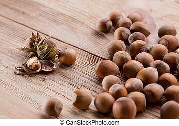 Hazelnuts on brown wooden table - Hazelnuts on wooden table