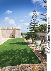 Mdina - Old city walls and green well kept lawn on a sunny...