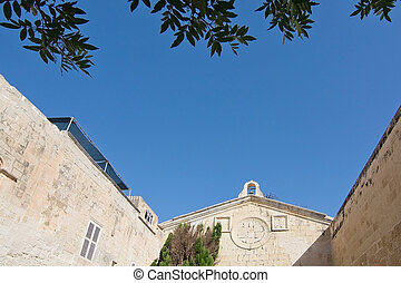 Mdina - Old building, foliage and blue sky inside old city...