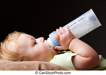 Young guy drinking - Boy drinking his bottle making a mess