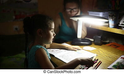 teen in the evening doing homework girl lessons draws light...