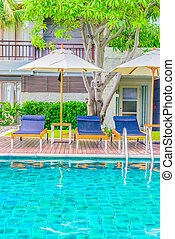 Outdoor Swimming pool and umbrella with chair deck in hotel...