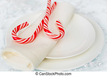 Christmas table - Two red and white striped candy canes lie...