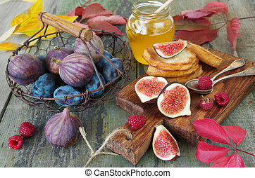Healthy Eating - Ripe figs and blue plums in a vintage metal...