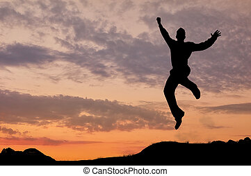 Silhouette of a man jumping in the sunset - Business...