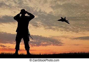 Silhouette of a soldier and an airplane looking through...