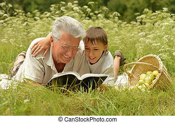 Grandfather and grandson reading book - Grandfather and his...