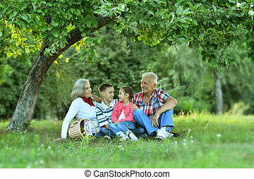 Family  in summer park with apples