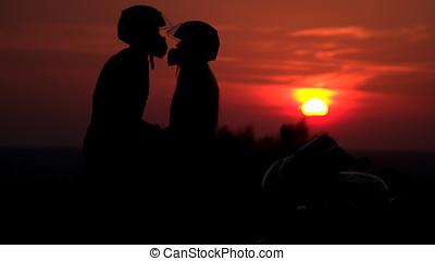 two mountain biker - comantic couple silhouette in sunrise -...