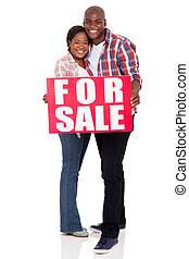 young african couple holding a for sale sign
