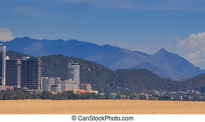 view of resort city against mountains from sand beach -...