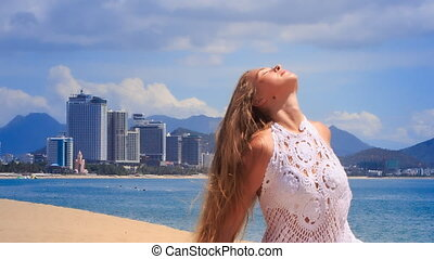 blonde girl in lace shows yoga asana smiles against sea