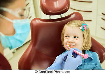 Little girl sitting in the dentists office. The dentist...