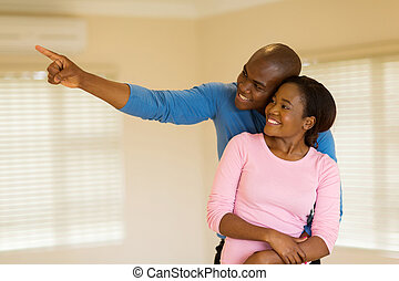 young african couple looking round their new house