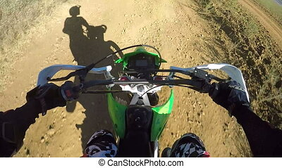 Point of View: Enduro rider in motorcycle protective gear riding bike on dirt track