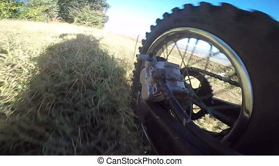 Offroad bike riding on dirt track rear wheel point of view