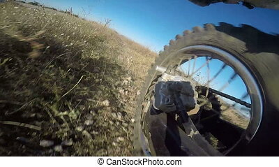 Enduro racer riding bike on dirt track jumping rear wheel...