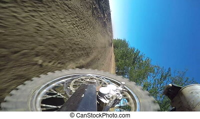 Enduro racer riding bike on dirt track kicking up dust rear...