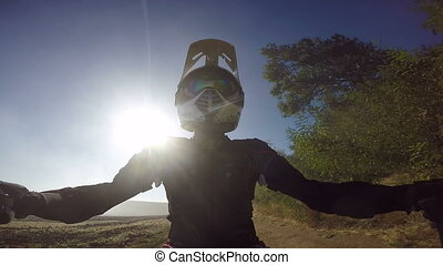 PoV: Enduro racer kicking up dust riding bike on dirt track against the sun