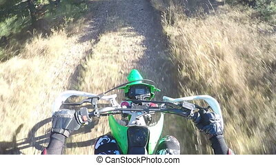 PoV: Enduro racer riding bike on dirt track through the...