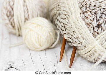 Skeins of wool yarn and knitting needles from bamboo on a...