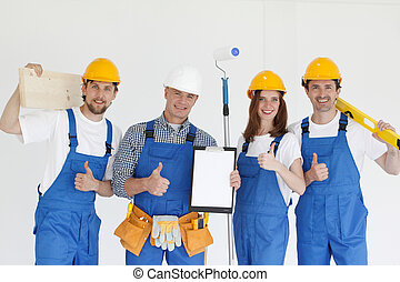 Group of smiling builders in hardhats with tools indoors