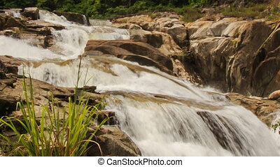 closeup view of waterfall among rocks in tropical park