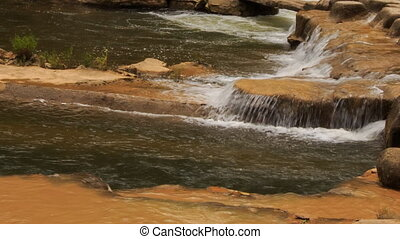 closeup stream falls on plane surface among stones in park -...