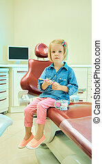 Little girl sitting in the dentists office - Little blond...