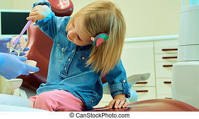 Little girl sitting in the dentists office learning to clean...
