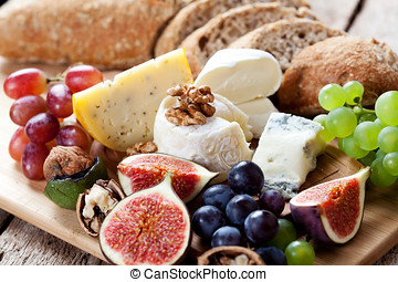 Cheese platter: variety of cheeses on wooden plate with...