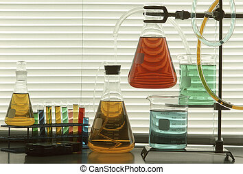 Scientific glassware and tubes filled with colored liquids...
