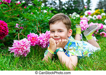 Thoughtful and dreamy boy is lying on the green grass in...