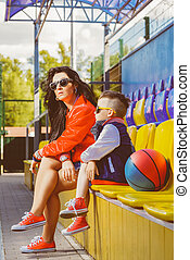Rapper attitude rap singer hip Hop Dancer performing. Stylish woman and little boy posing at basketball court. Warm toned photo