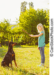 blonde girl playing with the dog or doberman in summer park....