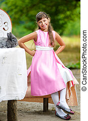 Girl sits near table and looks at the rabbit. Alice in Wonderland concept