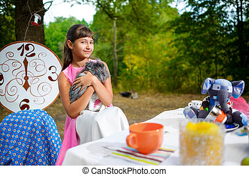 Girl sits at table and holding a rabbit. Alice in Wonderland concept