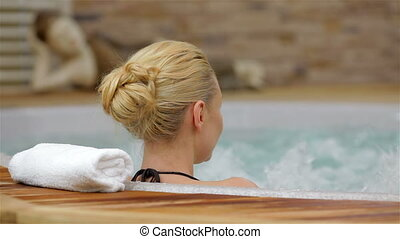 Back view of a woman enjoying jacuzzi