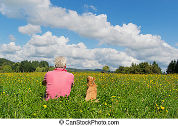 Man with dog - Senior man sitting with dog in landscape