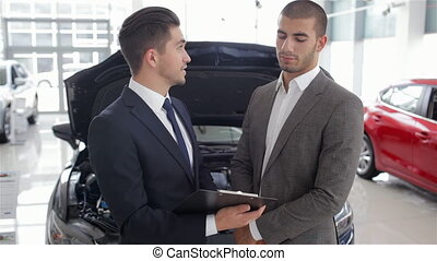 Salesman in a motor show - Young man with a salesman in a...
