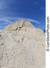 Sand mound - gravel sand mound against blue sky
