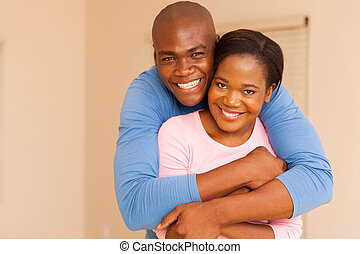 african american man hugging his wife - portrait of handsome...