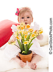Baby girl with daffodils in a pot