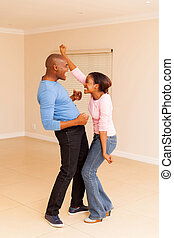 black couple dancing at their new home - excited black...