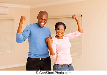 young african couple holding fist - cheerful young african...